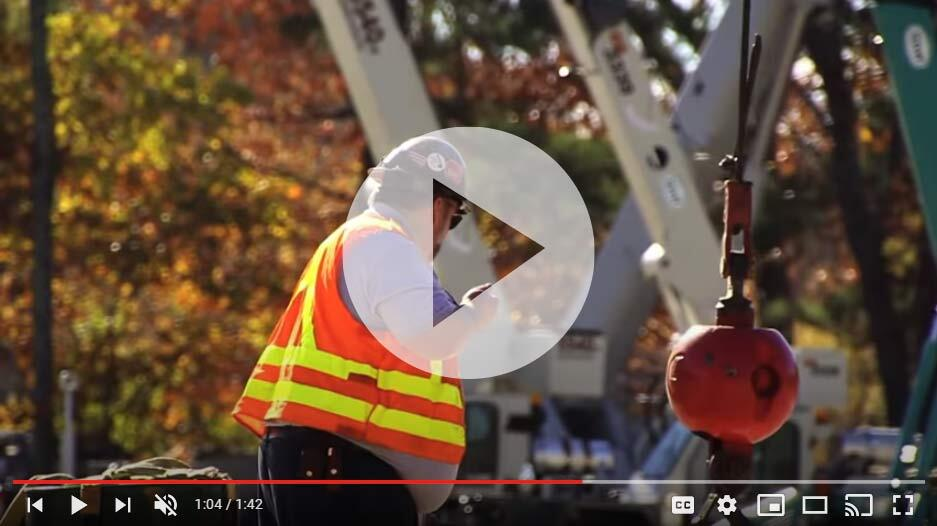 Video thumbnail of signalperson assisting with operating crane. He is wearing an orange and yellow safety vest.